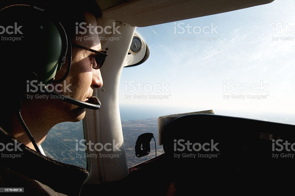 Pilot in the cockpit of an airborne small plane stock photo
