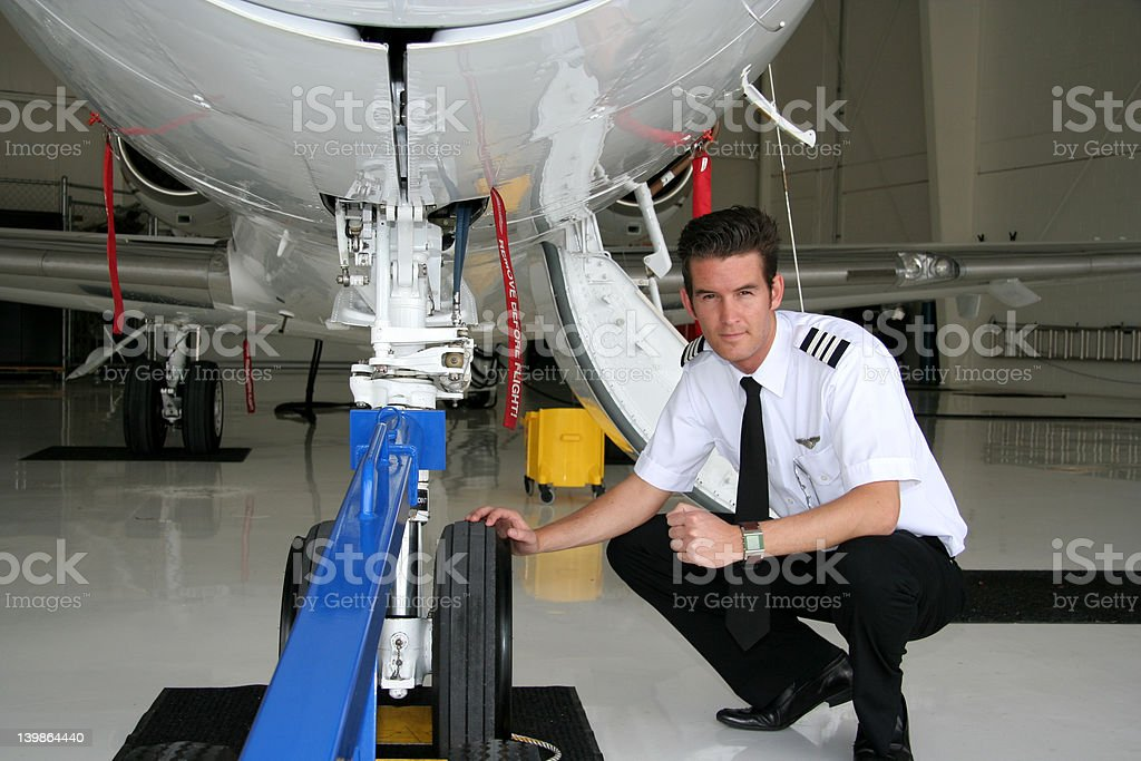 Pilot inspecting airplane royalty-free stock photo