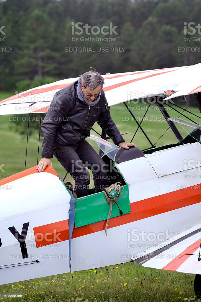 Pilot of a biplane happy after landing stock photo