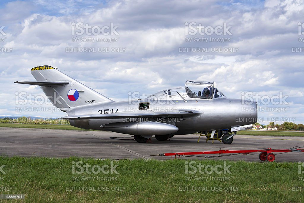 Pilot of jet fighter aircraft Mikoyan-Gurevich MiG-15 standing on runway stock photo