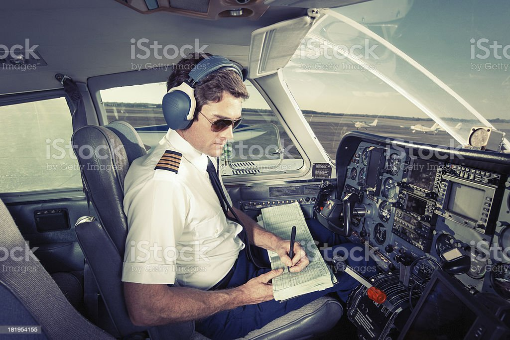 Pilot of Small Commuter Aircraft Writing in Log Book royalty-free stock photo