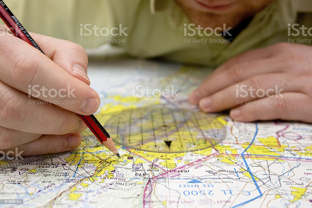Pilot plotting a course on map stock photo
