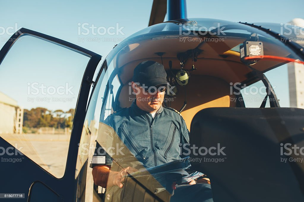 Pilot reading map in a helicopter cockpit stock photo