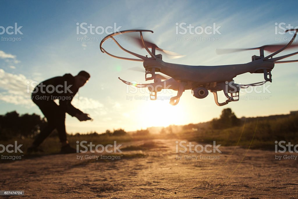 Pilot running drone at sunset light, free space stock photo