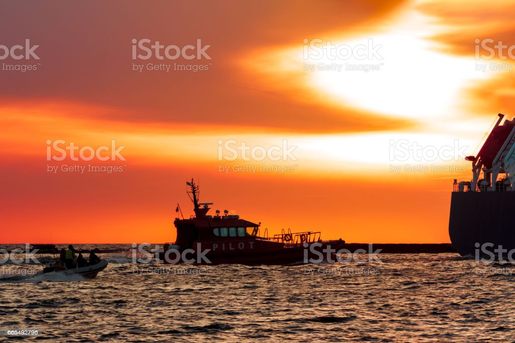 Pilot ship catches big container ship stock photo