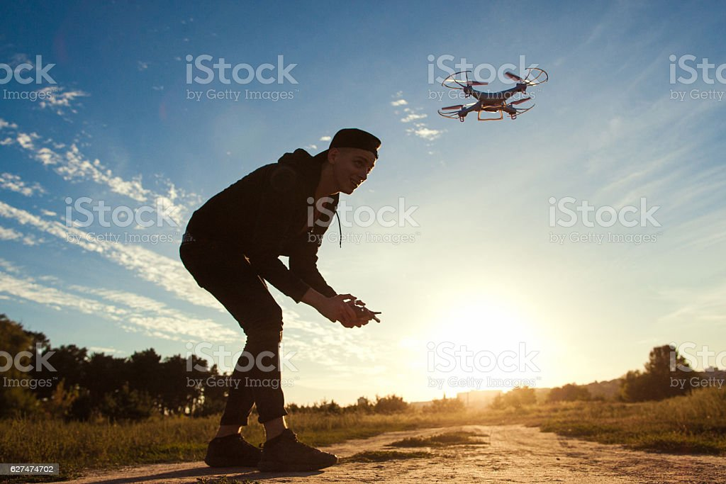 Piloting drone in field, sunset flare, free space stock photo