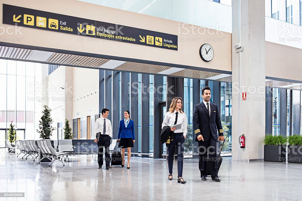 Pilots and flight attendants walking at the airport stock photo