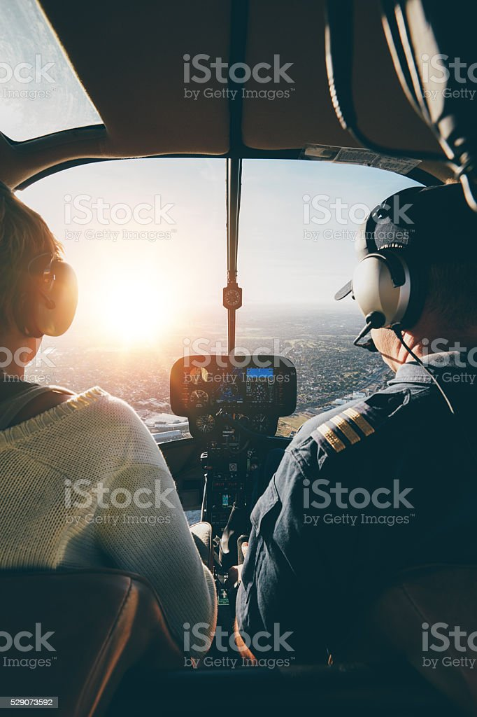 Pilots flying a helicopter on sunny day stock photo