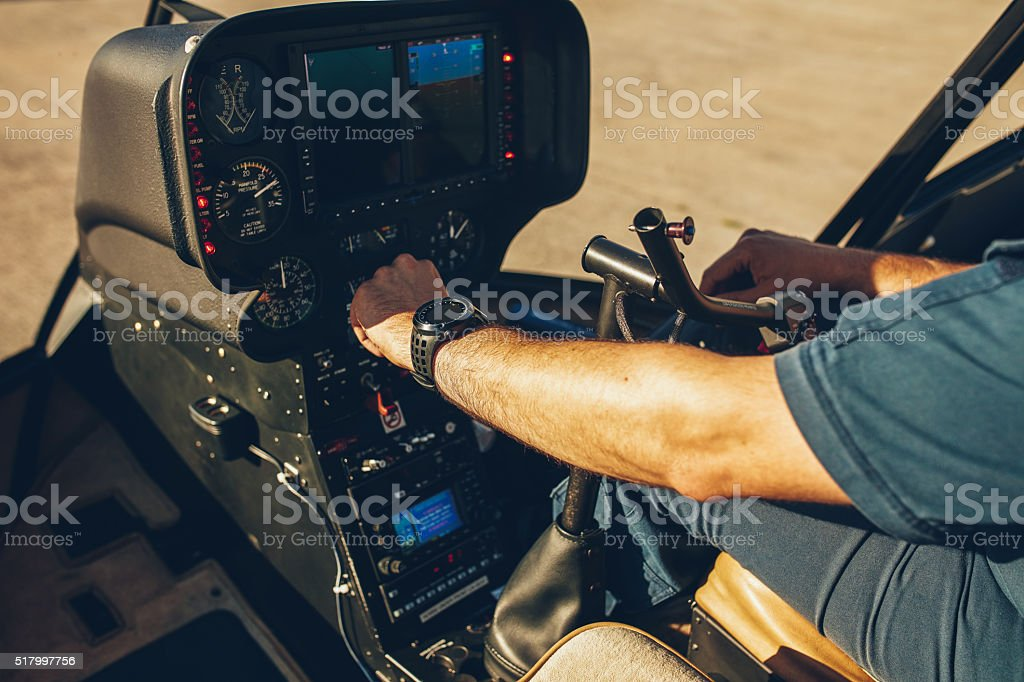 Pilot's hand on an helicopter instrument panel. stock photo