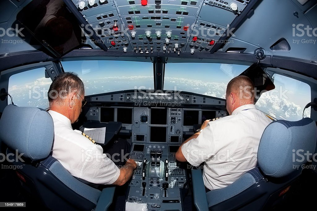 Pilots in the cockpit of commercial airplane stock photo