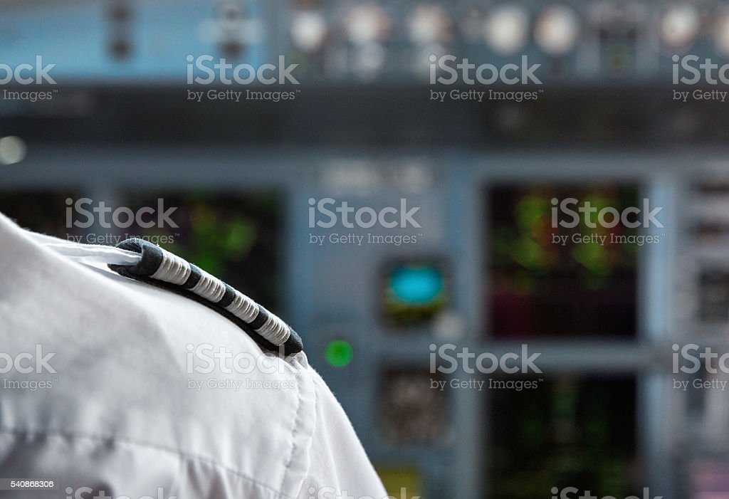 Pilot's shoulder with a badge in an aircraft cockpit. stock photo