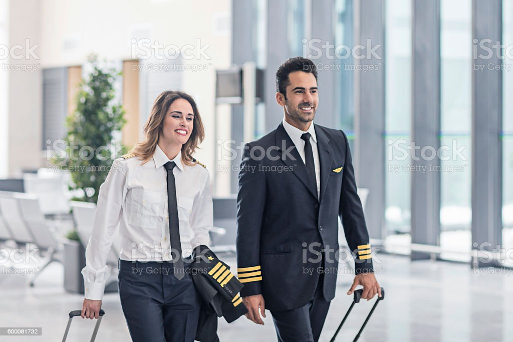 Pilots walking in the airport terminal. stock photo