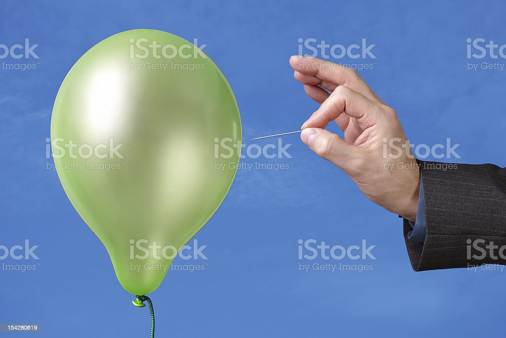 A pin being used to pop a green balloon stock photo