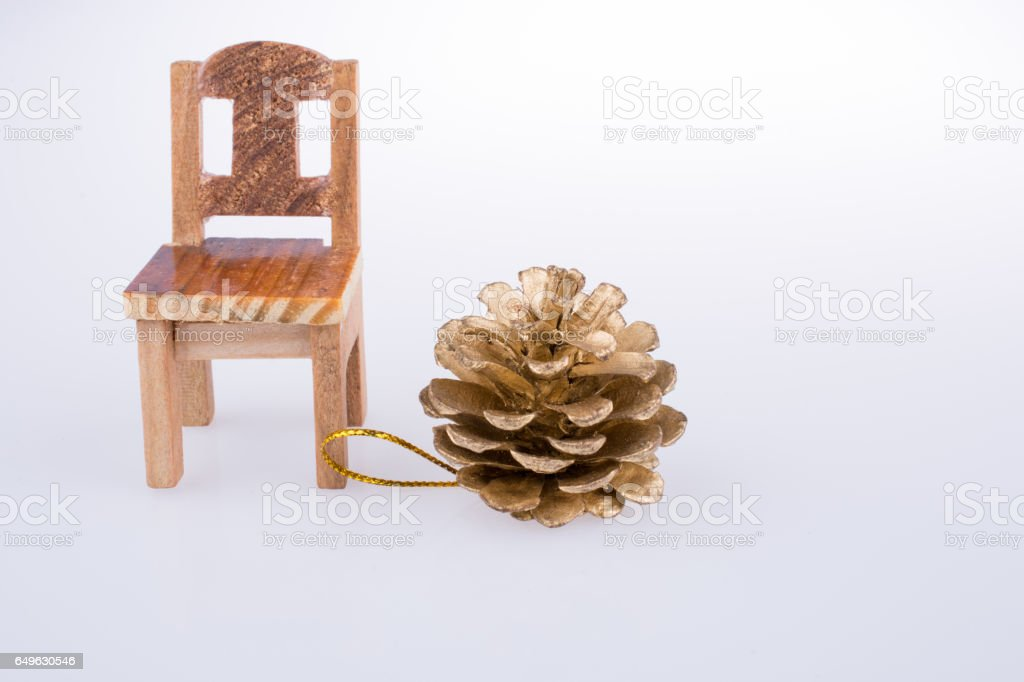 Pine cone bye the side of a little model chair stock photo
