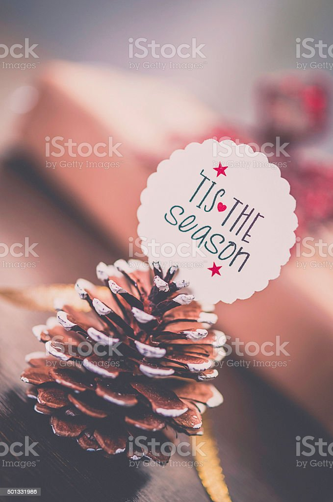 Pine cone with message in front of Christmas gifts stock photo