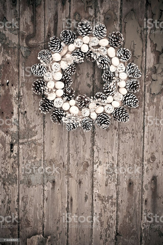 Pine cone wreath on rustic wood panelled door royalty-free stock photo