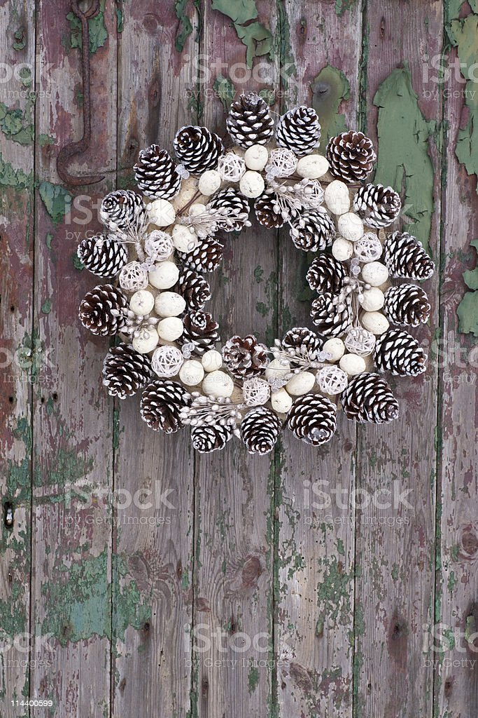 Pine cone wreath on rustic wood panelled door stock photo