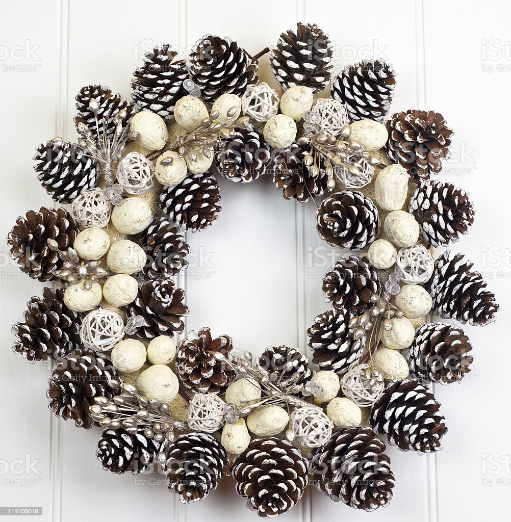 Pine cone wreath on white paneled wall royalty-free stock photo