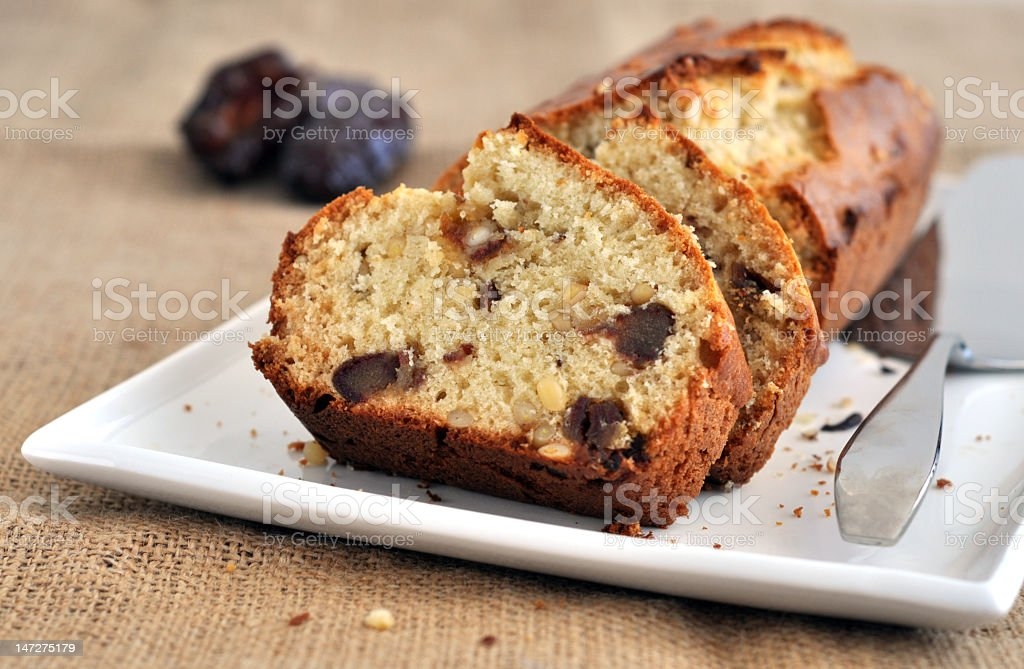Pine nut and date loaf cake on white plate with spoon royalty-free stock photo