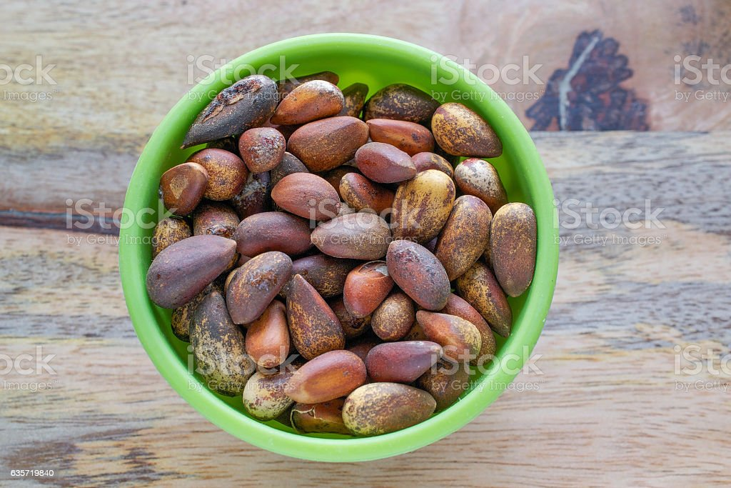 Pine nuts in green bowl stock photo