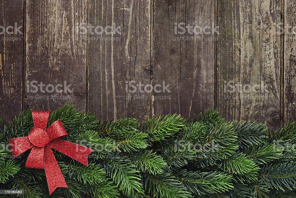 Pine tree with red glitter ribbon on old wooden background royalty-free stock photo
