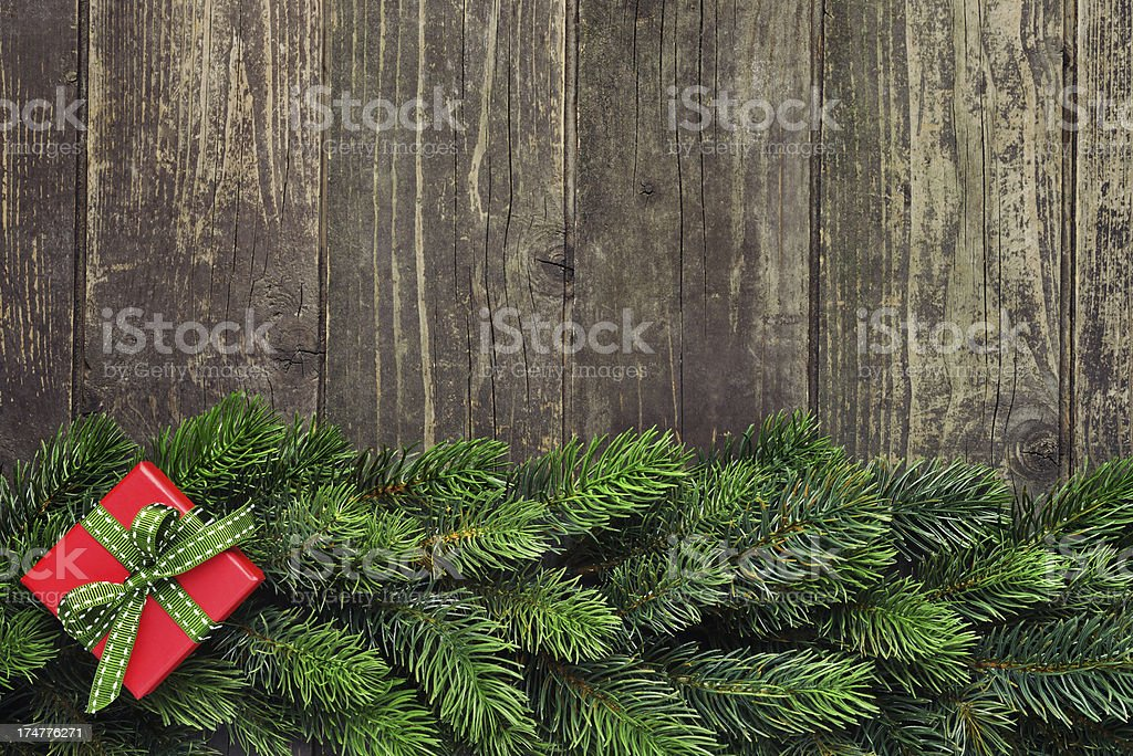 Pine tree with red present on old wooden background royalty-free stock photo