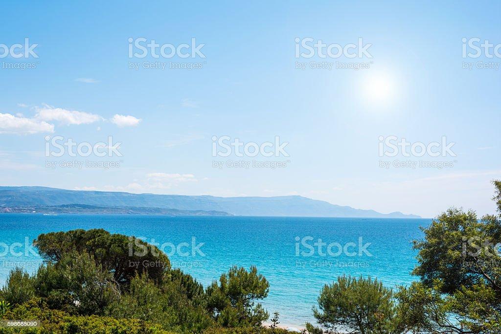 pine trees and blue sea in Alghero coastline stock photo