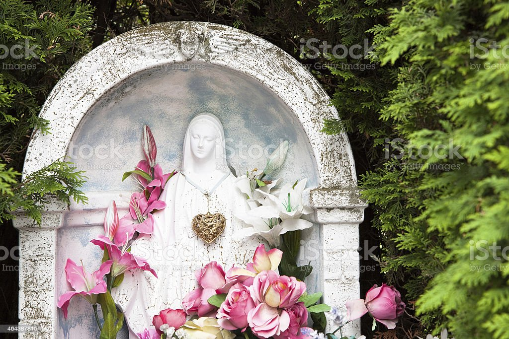 Pine wooded cemetery Virgin Mary with pink lilies royalty-free stock photo