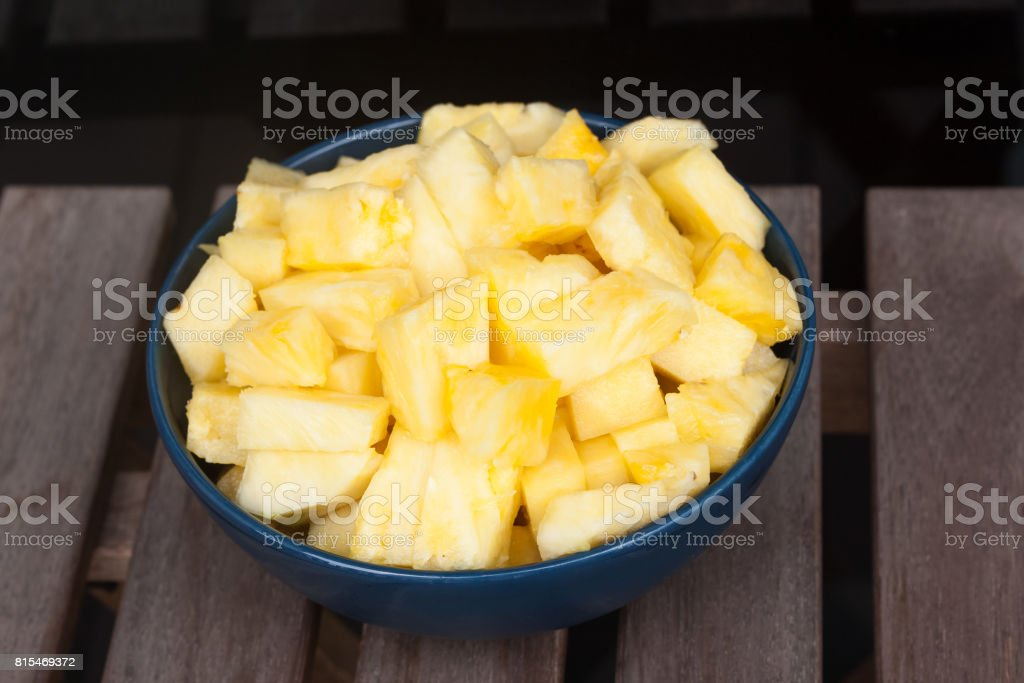 Pineapple cubes in a blue bowl stock photo