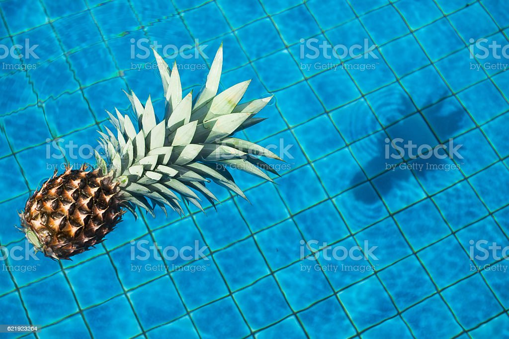 Pineapple floating in water stock photo