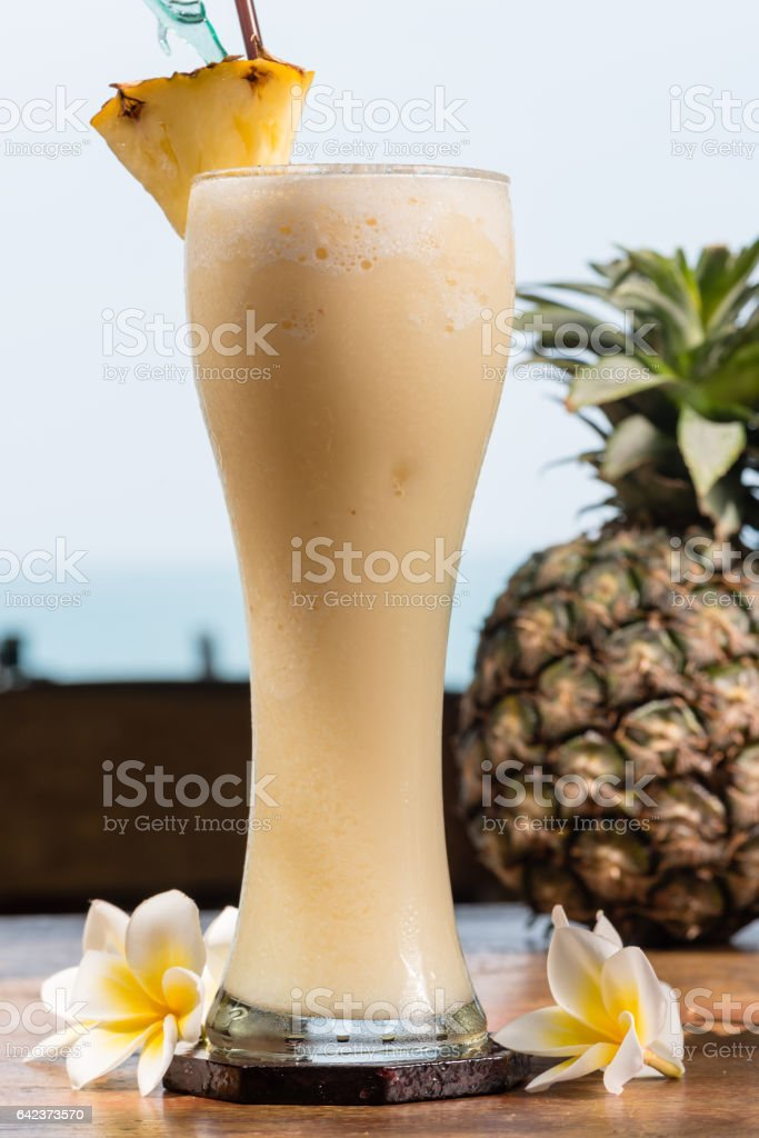 Pineapple milkshake in glass on table stock photo