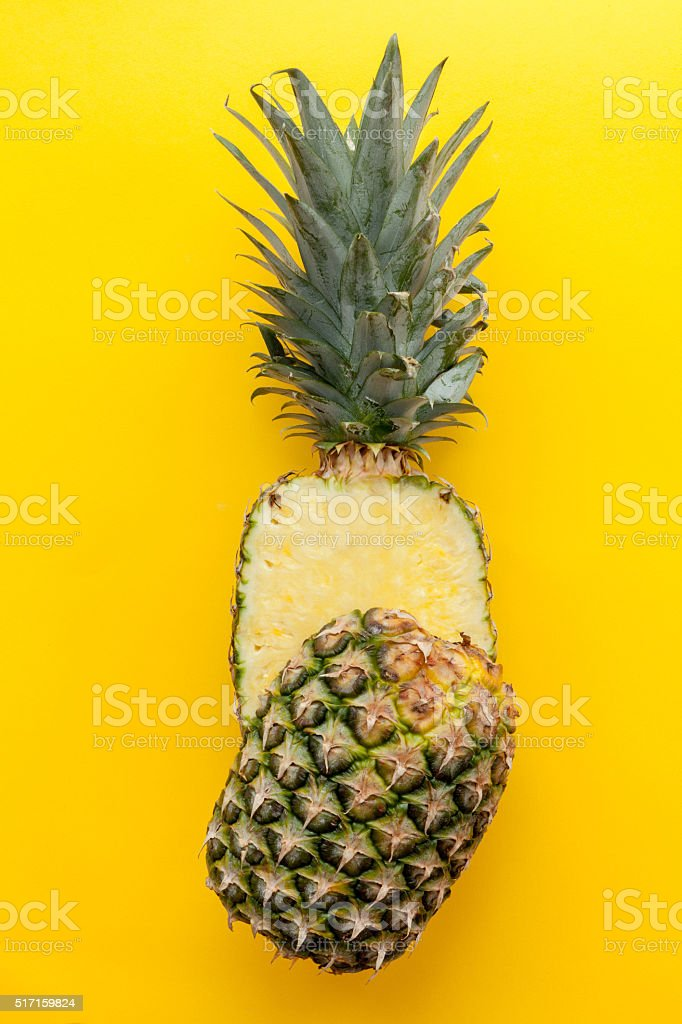 Pineapple on a solid yellow background stock photo