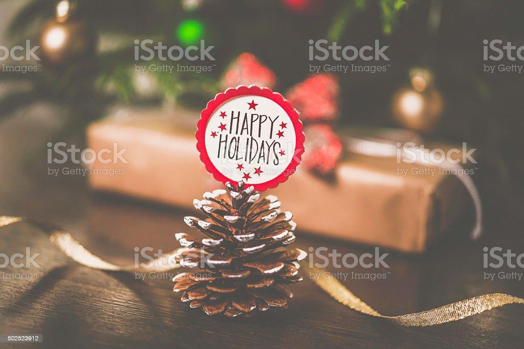 Pinecone with message in front of Christmas tree and gifts stock photo