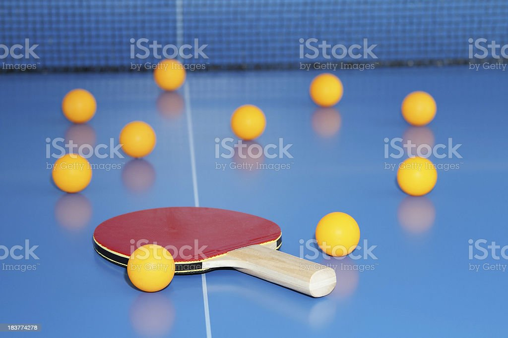 Ping pong paddle and balls on blue table tennis top. stock photo
