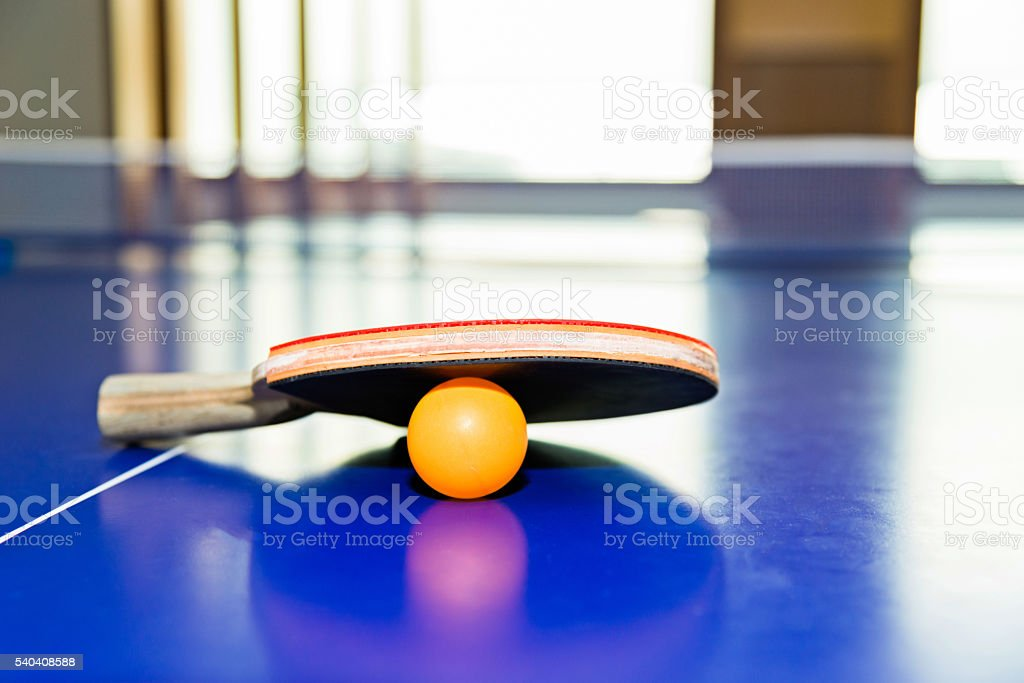 Ping-Pong paddles with ball on table stock photo