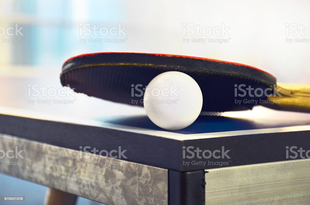 Pingpong racket and ball highlighted on a blue pingpong table stock photo
