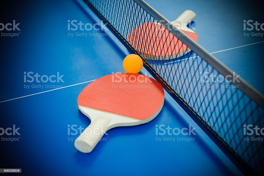 pingpong rackets and ball highlighted on a blue pingpong table stock photo