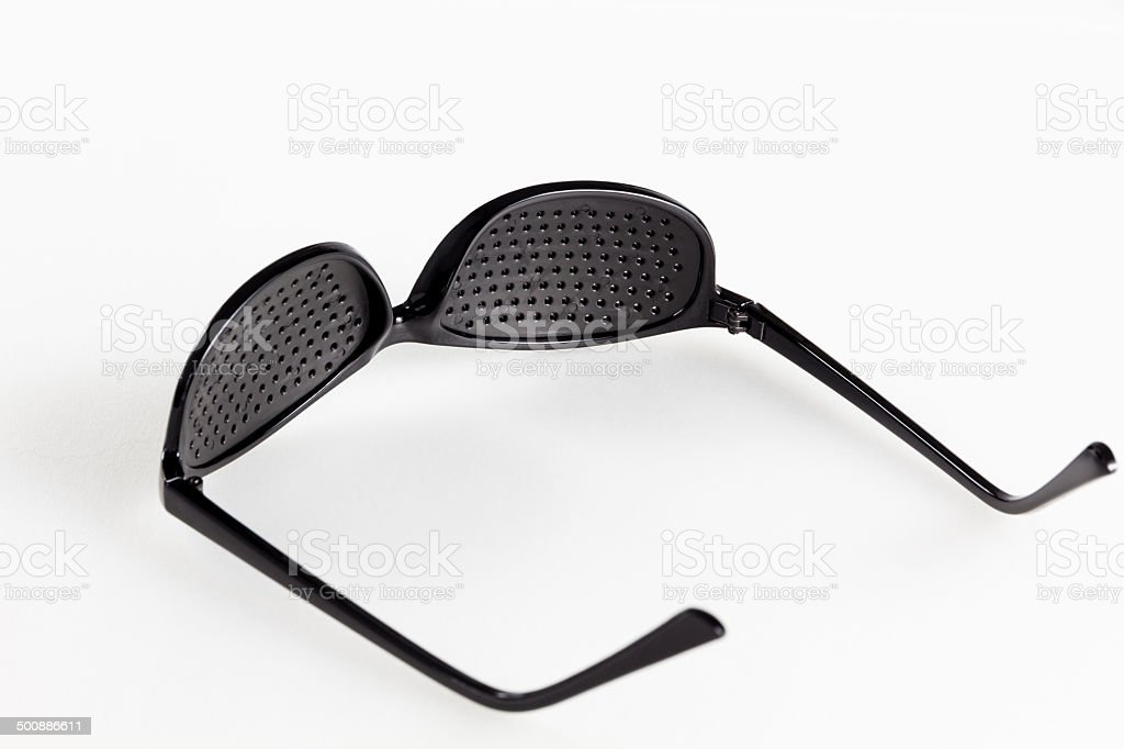 Pinhole eyeglasses help relaxing weary eyes, on white background. stock photo