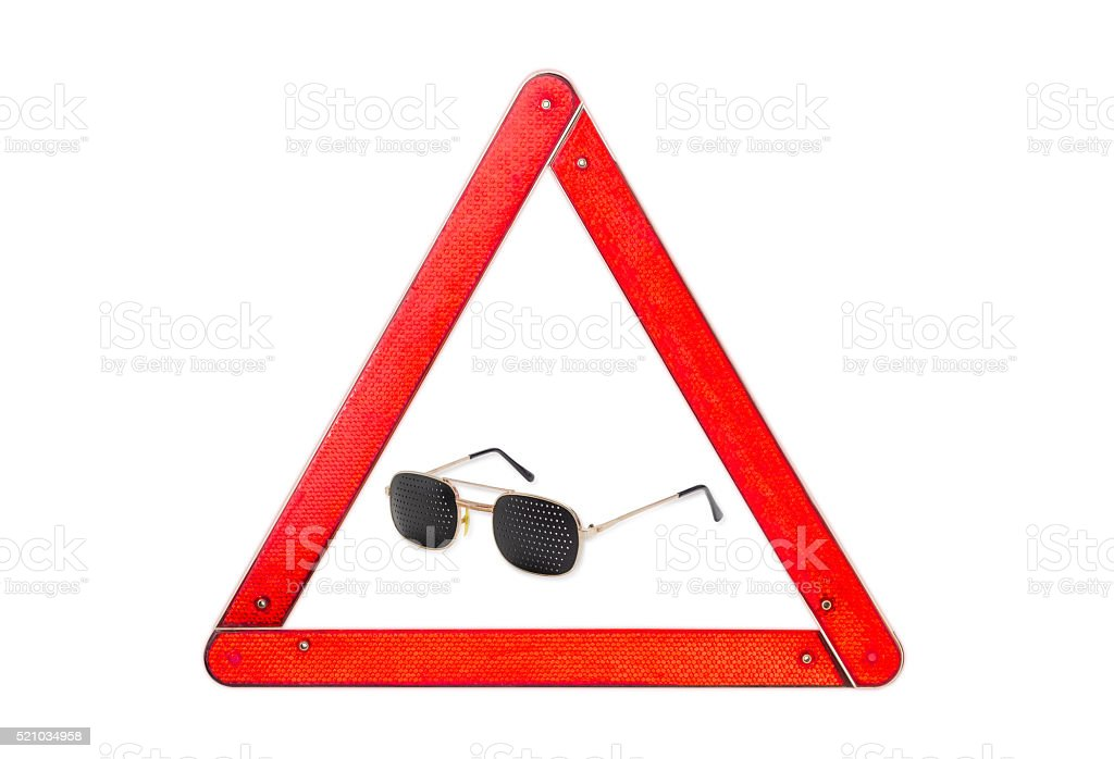 Pinhole glasses among warning triangle on a light background stock photo