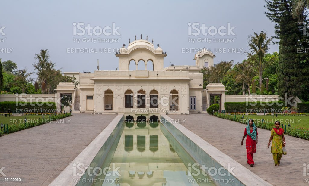Pinjore Gardens (Yadavindra Gardens), built for the concubines of the ruler. The Palace reflected in the water. Hindu women walk on the terraces. stock photo