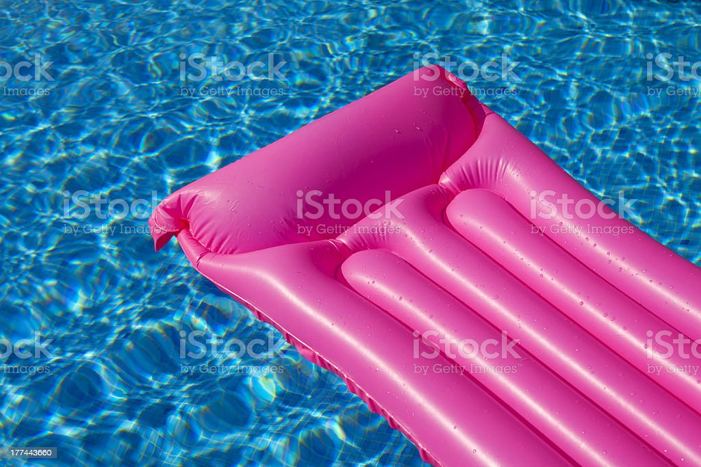 Pink air bed mattress in swimming pool stock photo