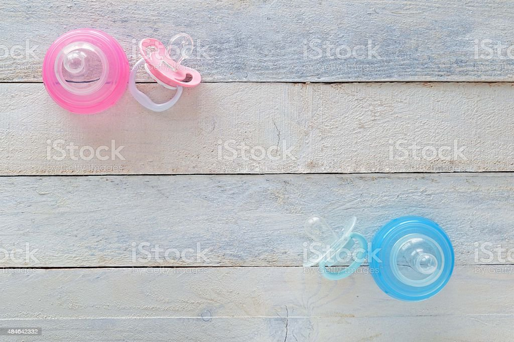 Pink and Blue pacifiers and baby bottles on white wood stock photo
