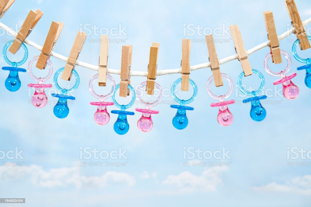 Pink And Blue Pacifiers Hanging On A Clothesline royalty-free stock photo