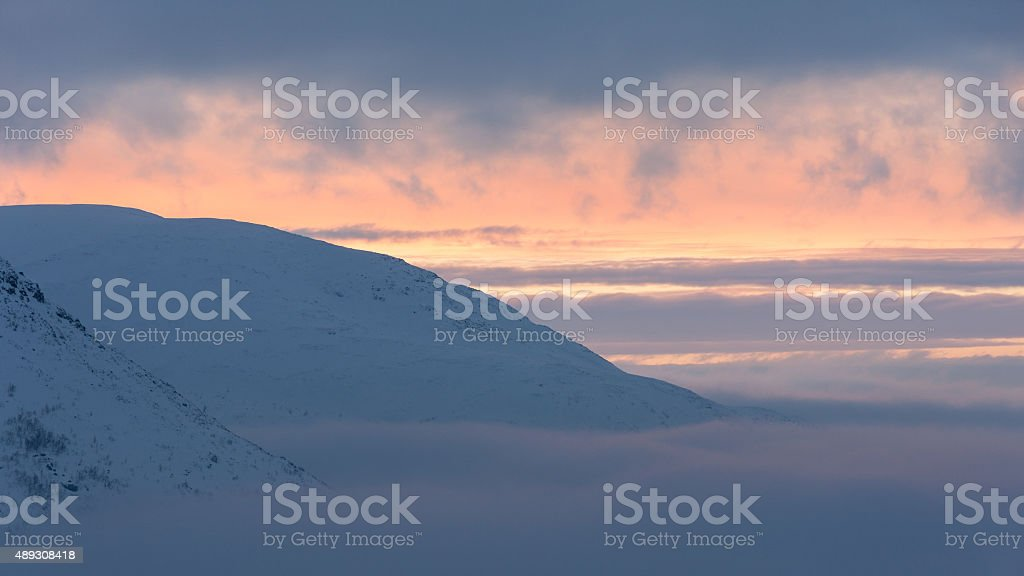 Pink and orange sunset in snow-covered mountains stock photo