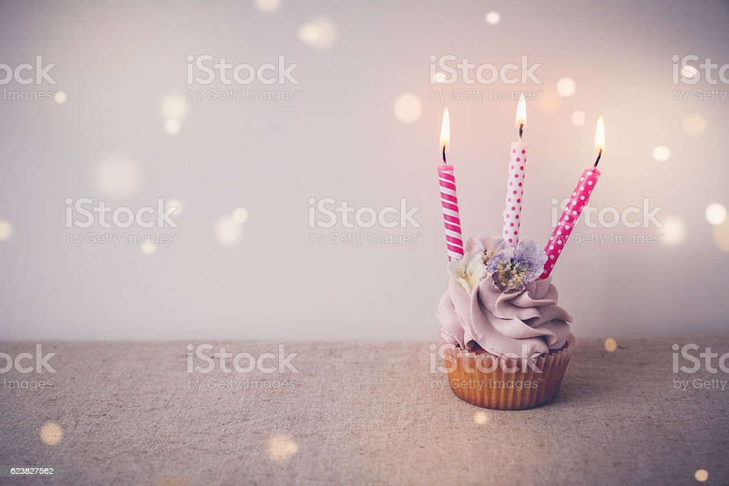 Pink and purple Birthday cupcake with three candles, fairy light stock photo