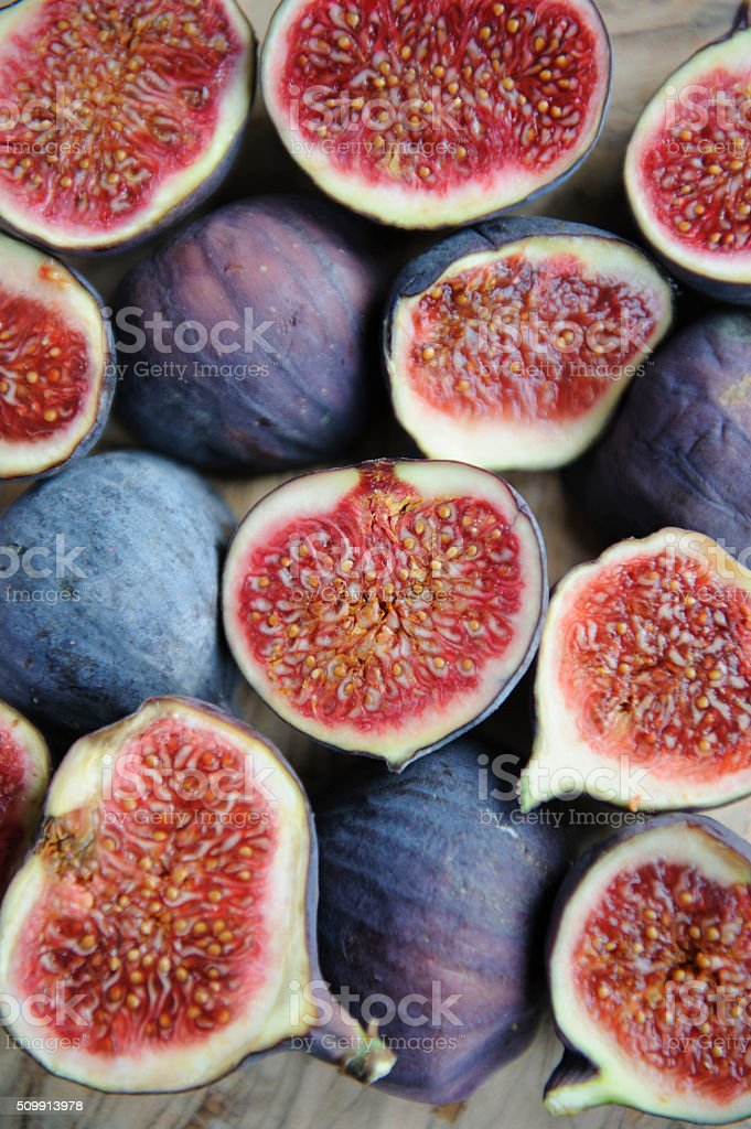 Pink and purple figs on a wooden board stock photo