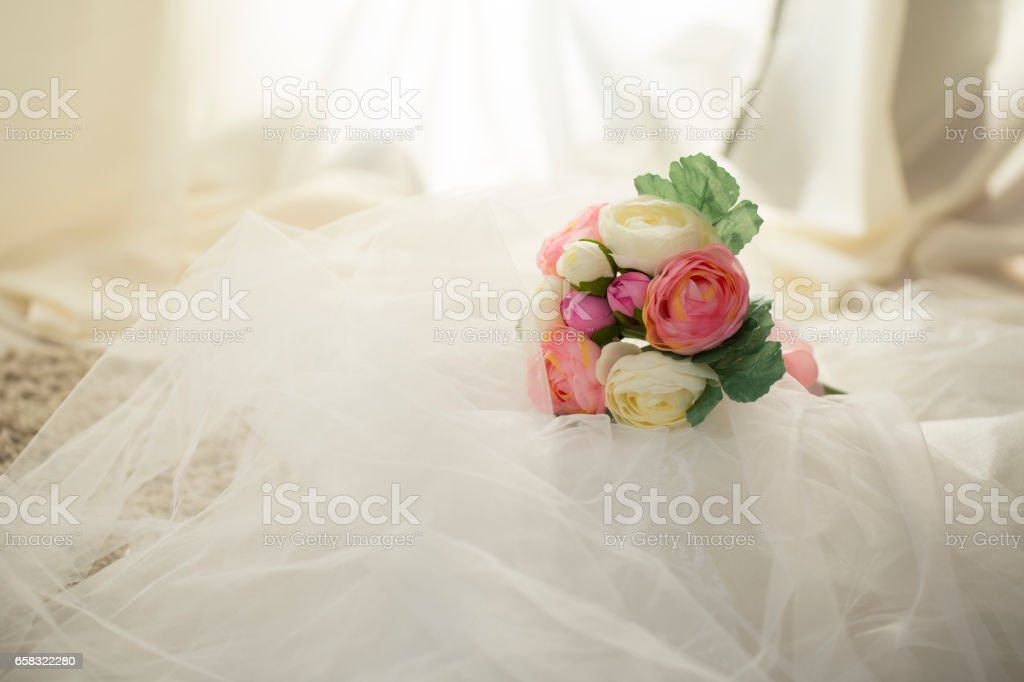 Pink and white flowers hand bouquet on white lace veil background. stock photo