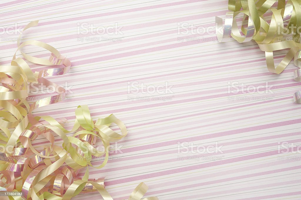 Pink and yellow ribbon curls on striped background royalty-free stock photo