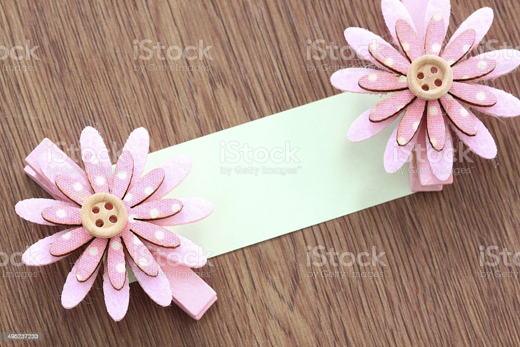 Pink artificial flowers and note paper stuck on dark wood. royalty-free stock photo