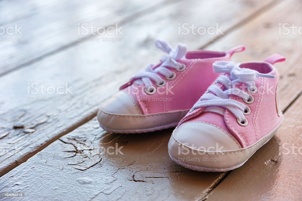 Pink baby girl shoes on a wooden floor outdoors stock photo